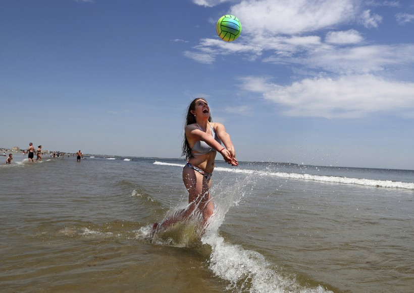 Woman playing volleyball in water on vacation