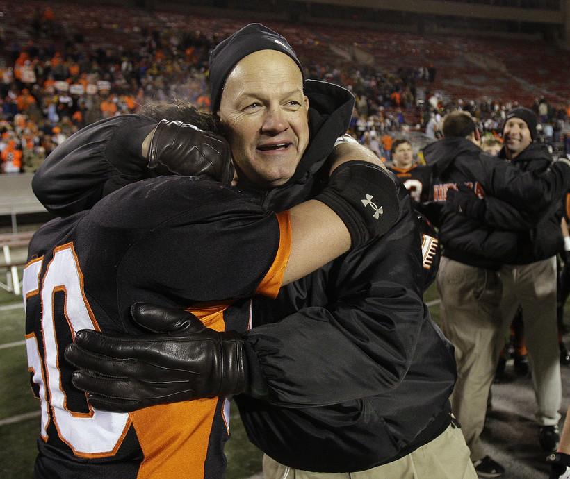 Wautoma/Faith Christian coach Dennis Moon hugs Garrett Bickford (50) after the WIAA Division 4 high school football championship game