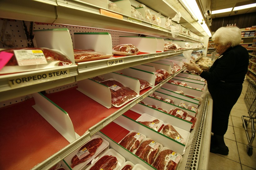 Person scanning meat counter at grocery store