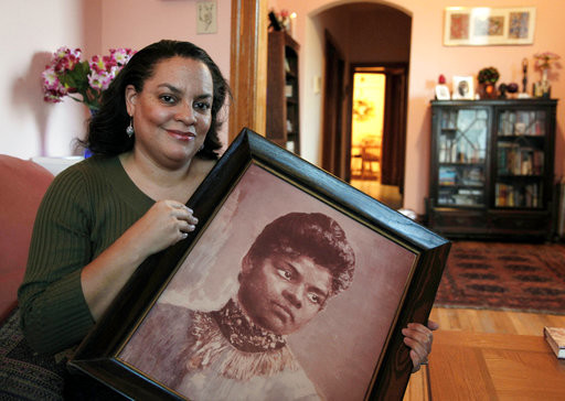 In this Dec. 2, 2011 file photo, Michelle Duster, great-granddaughter of civil rights pioneer Ida B. Wells who led a crusade against lynching during the early 20th century, holds a portrait of Wells in her home in Chicago's South Side.