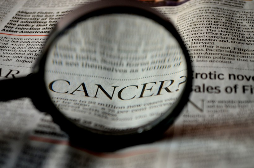 Newspaper with word cancer magnified