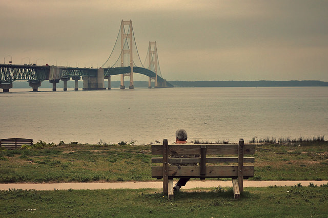 Person sitting alone on a park bench in Michigan