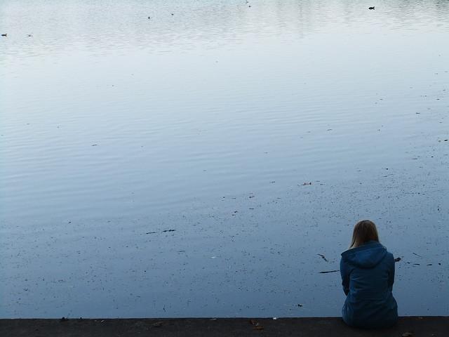 Woman sitting alone near the water