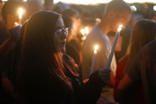 Attendees raise their candles at a candlelight vigil