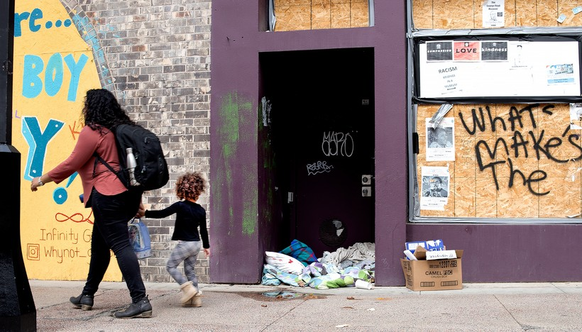 A woman and child pass by an abandoned storefront on State Street in Downtown Madison