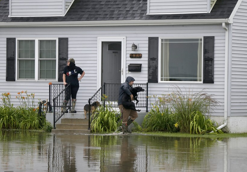 Jason O'Donnell carries his dog over the flood water