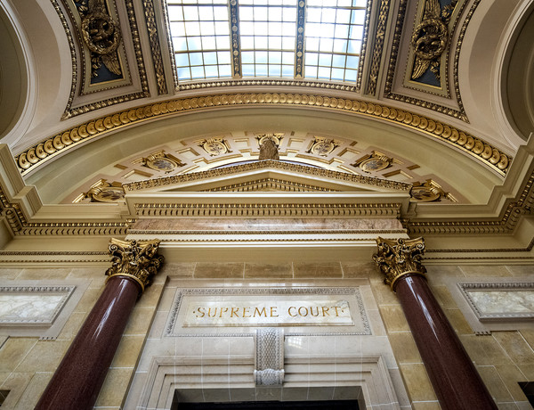 """""""Supreme Court"""" is written above a door inside the Wisconsin State Capitol."""