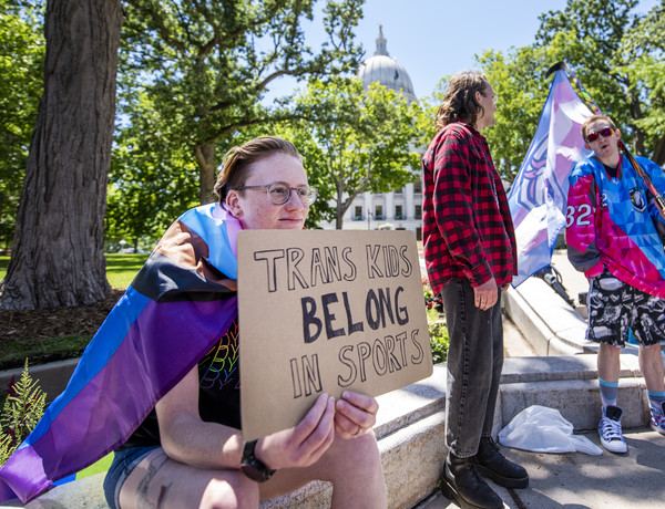 """A protester holds a sign that says """"Trans Kids Belong In Sports."""""""