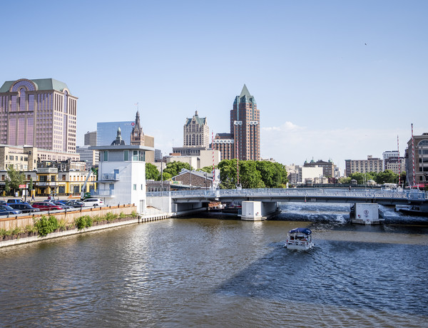 A blue sky backdrops tall buildings as a boat makes ripples in the Milwaukee River.