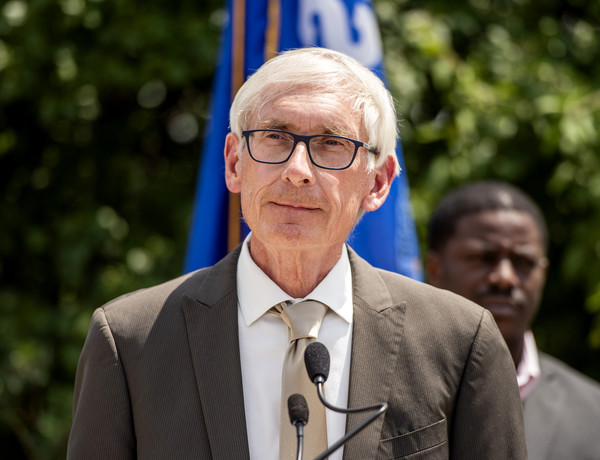 Tony Evers looks over at the reporters asking questions during a press conference.