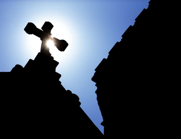 The silhouette of a cross on a Catholic church