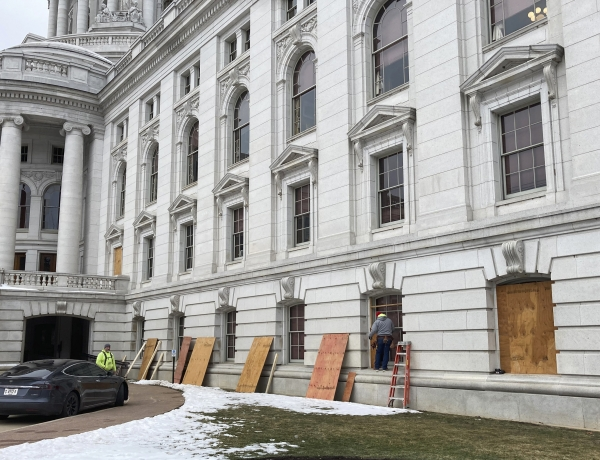 Workers begin boarding up the Wisconsin state Capitol