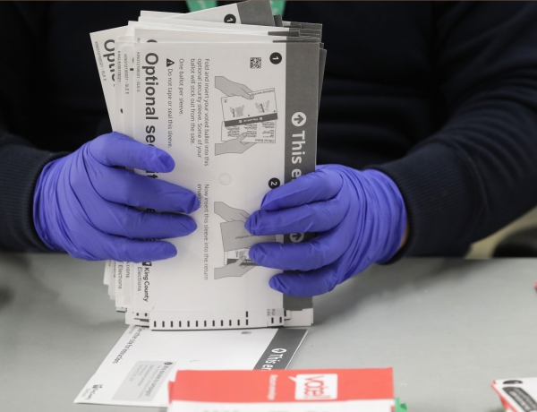 A worker wears gloves while handling ballots
