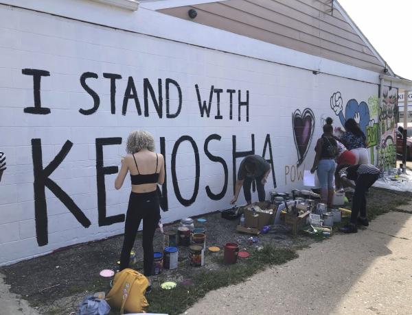 Volunteers paint murals on boarded-up businesses in Kenosha