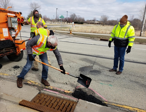 Wisconsin Gov. Tony Evers (foreground) fills potholes during a recent series of events in northern Wisconsin designed to highlight his 2021-23 budget proposal