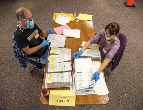 Election workers Jeff and Lori Lutzka, right, process absentee ballots