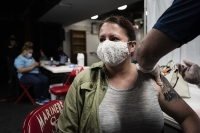A woman wears a face mask as she receives a COVID-19 vaccine.