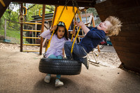 Two children swing on a tire swing. A child leans back as his blonde hair fans out behind him.