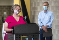 Satya Rhodes-Conway wears a mask while speaking at a podium. Joe Parisi stands off to the side, also in a face mask.