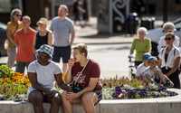 People sit and stand near flowers in on a sunny day in downtown Madison.
