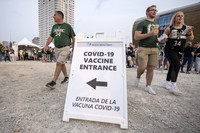 """A sign says """"COVID-19 Vaccine Entrance"""" as fans walk by holding drinks."""
