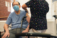 Marvin Marcus, 79, a resident at the Hebrew Home at Riverdale, receives a COVID-19 booster shot.