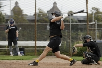 Baseball player swings at ball while wearing face mask