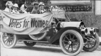 "Suffragists in a vehicle with a sign reading ""Votes for Women"""