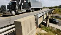 Semi-trailer truck drives on a highway bridge over an interstate