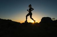 A woman runs up a trail during sunset.