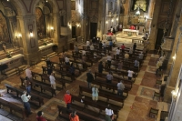 parishioners attend mass with significant space between them