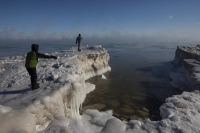 A young boy tosses a chunk of snow into Lake Michigan