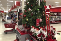 Shoppers wearing masks walk past a display of Christmas decorations at a Target store
