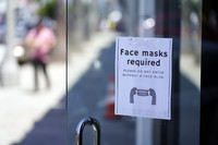 A sign advises shoppers to wear masks outside of a store