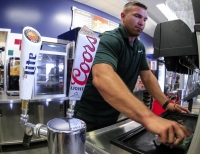 Trevor Hilger cleans a concession stand next to beer taps