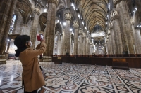 A tourist wearing a face mask takes pictures inside the Duomo gothic cathedral