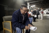 Unionized hospitality workers, including Luis Estrada, wait in lineto apply for unemployment