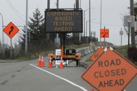 A sign directs vehicles toward a drive-up testing site at the Tacoma Dome in Tacoma, Wash