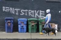 "A pedestrian walks past graffiti that reads ""Rent Strike"""
