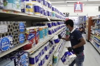 Jesus Padron wears a protective mask as he stocks shelves with toilet paper at the Presidente Supermarket