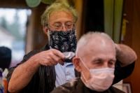 Barber cutting hair in a reopened Waukesha salon