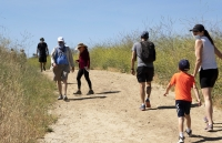 Visitors wear protective masks and social distance on a walk along a popular hiking trail along