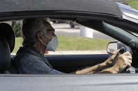 A man wears a mask while he is driving in Deerfield, Ill.