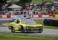 Paul Menard competes in a NASCAR race at Road America