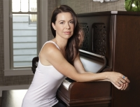Joy Williams sits at a piano