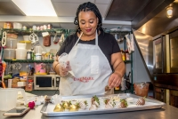 Adija Greer-Smith prepares chocolate-covered strawberries in the kitchen of her Milwaukee bakery.