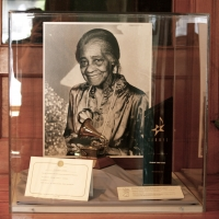 Photo of Elizabeth Cotten with her 1984 Grammy & 1996 Syracuse Area Music Award (Erie Canal Museum: Syracuse, NY)