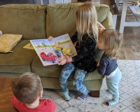 The Fogarty kids – from left to right, Odcar, Willa and Hazel – read books at home