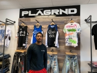 Synika Kirk poses PLAGRND, his clothing store in Green Bay