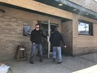 A man holds open a restaurant door.
